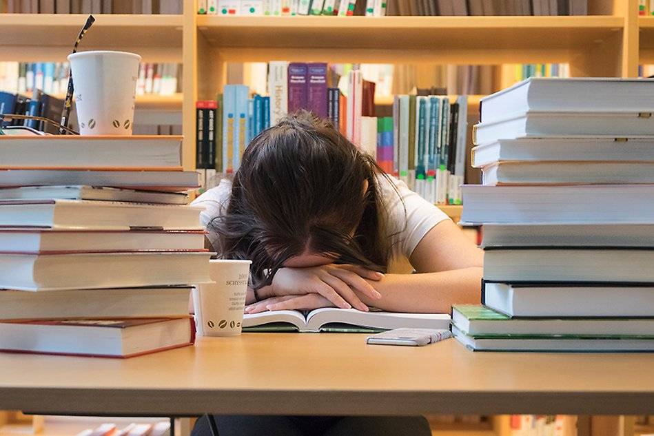 A person is sitting at a table, surrounded by book stacks, with her face down in a book. Photo.