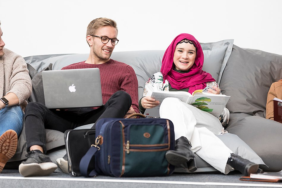 A younger man and a younger woman are seated in bean bags, each one of them with a computer in front of them. The man, who has glasses and light hair, looks at the woman's computer screen. The woman looks into the camera and is wearing a dark pink shawl around her head. Photo.