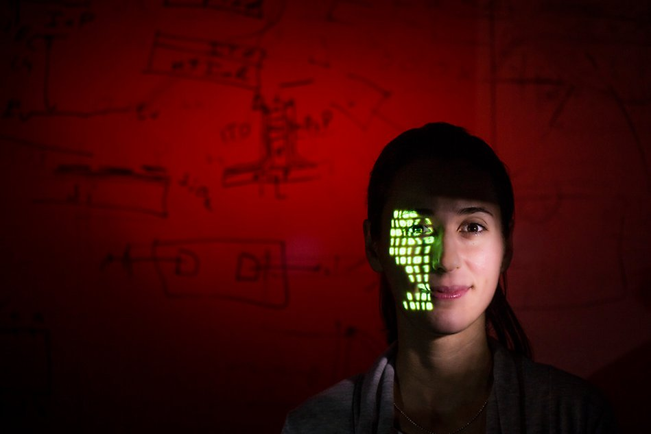 Picture of a woman with a projection of green light in the face. Photo.
