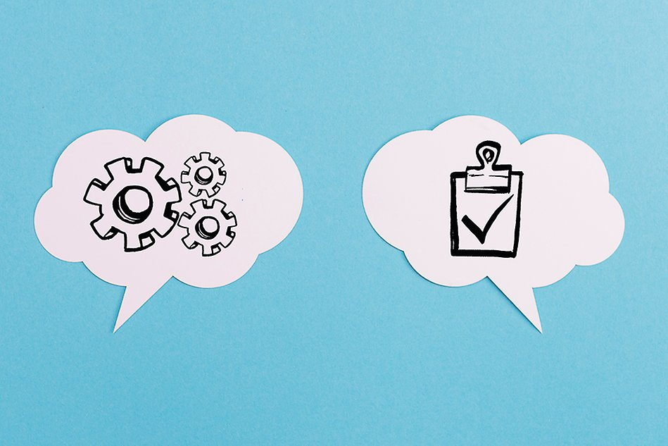 Speech bubble with three cogwheels next to speech bubble with tick symbol, on blue background