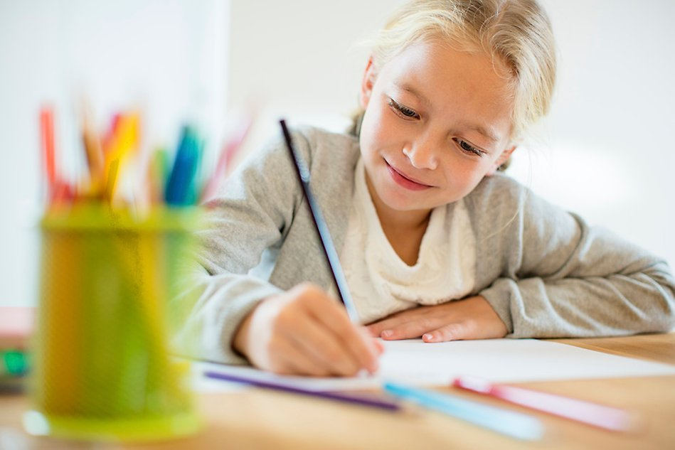 Colourful pens, blonde girl writing at a table. Photo.
