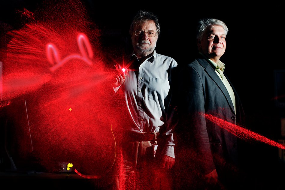 Two men with a black background, and red lasers.