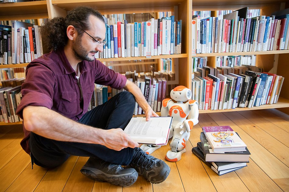 Man sitting on the floor, reading with a small robot.