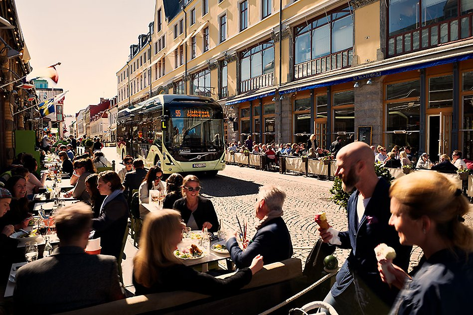A bus is driving in a city. People are sitting outside at restaurants along the way. Photo.