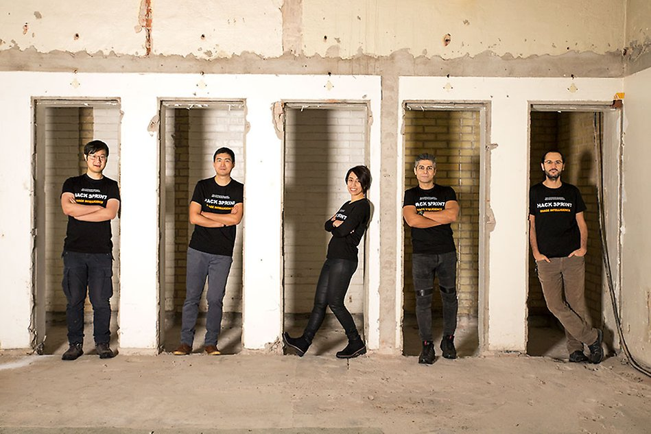 Five people standing on a row, in doorways. Smiling and looking into the camera. Photo.