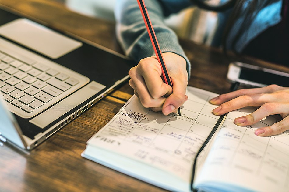 A hand is seen writing with a pencil in a calendar. To the left is a laptop. Photo.