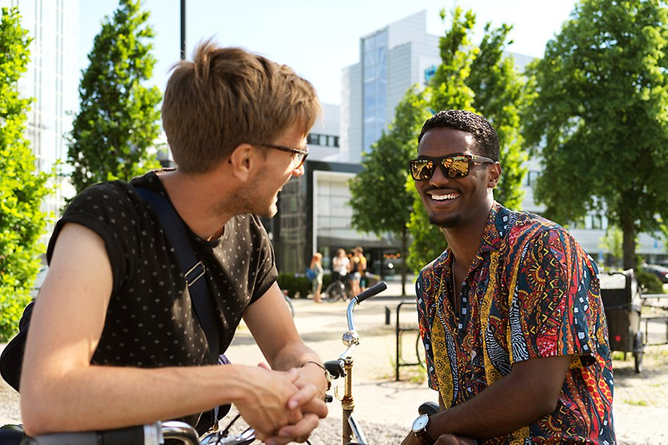 Two men talking and laughing, the Halmstad University main entrance can be seen in the background. Photo.