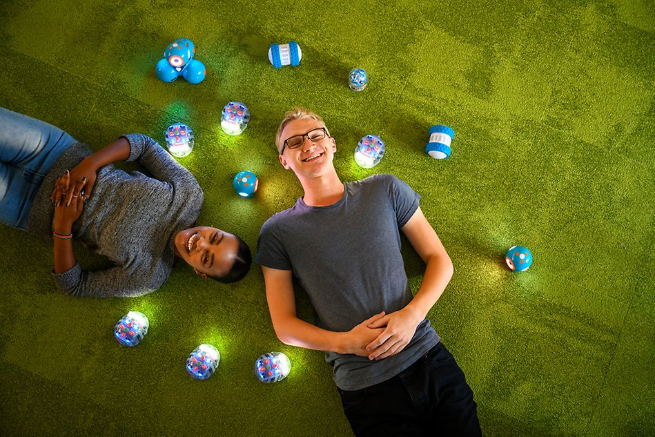 A male and a female student lying on a green mat, with electronic robots around them. Photo.