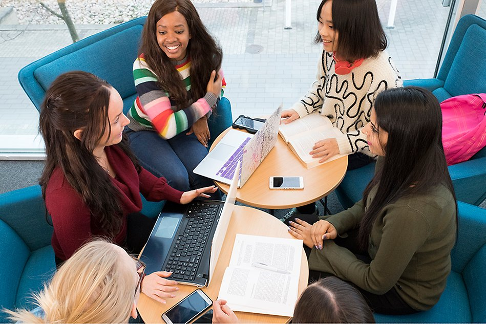 Six younger women are sitting around a table talking to each other. The picture is taken from above and the table is full of mobile phones, computers and books. Photo.