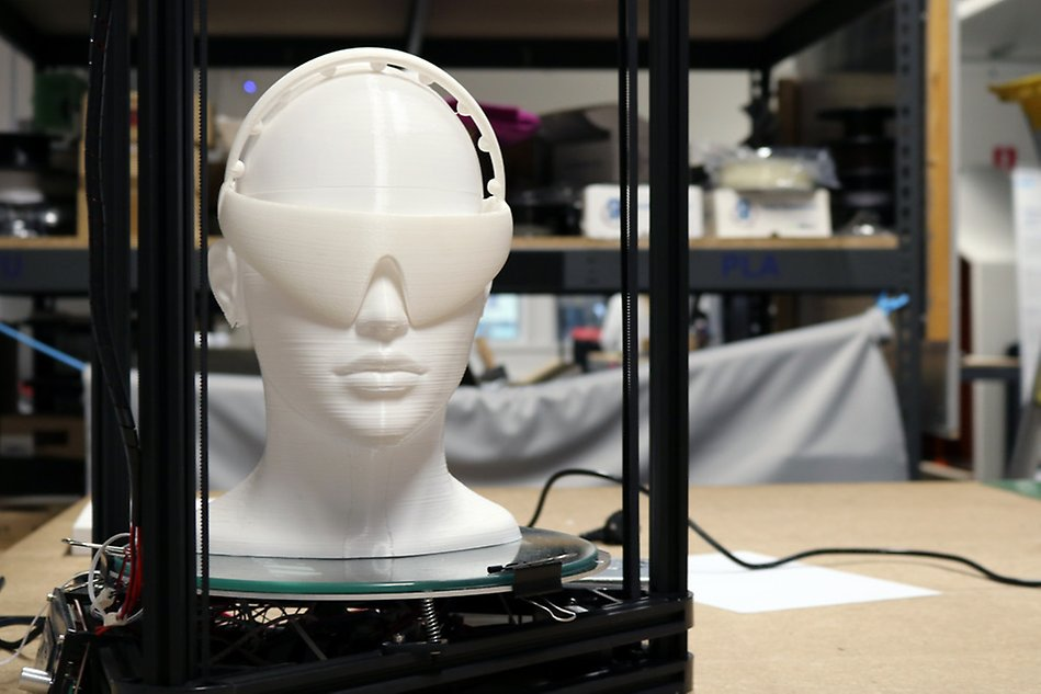 3D printer printing a model of a human head in white plastic. Photo.