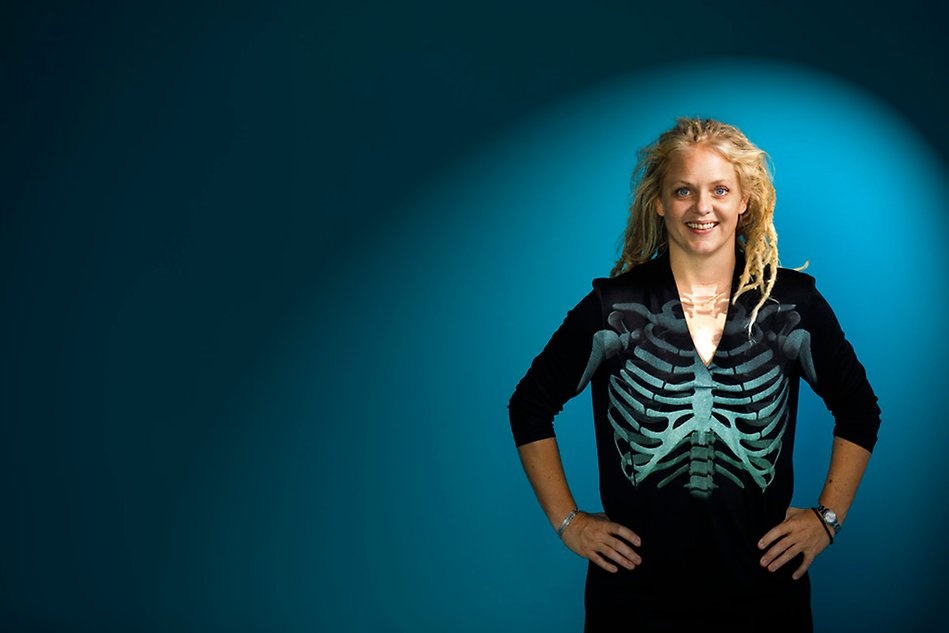 Blond woman standing against a blue background, an x-ray image of a human torso being projected onto her body. Photo.